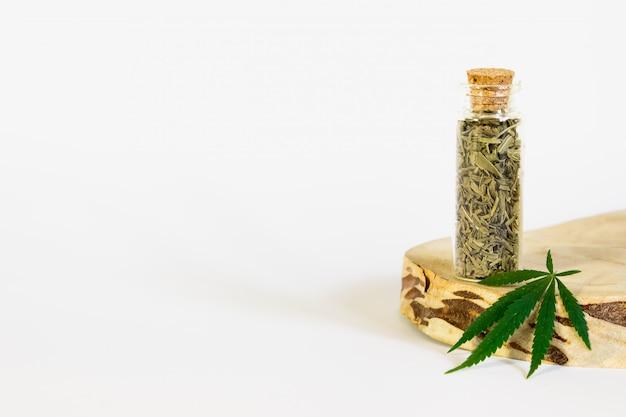 Grünes hanfblatt und getrocknete blätter in einem glas