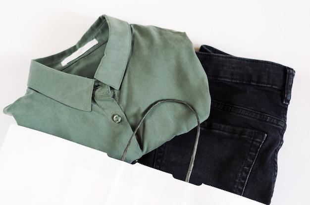 Grünes hemd mit einer weißen marke und schwarzen jeans in einer papiertüte auf weiß.