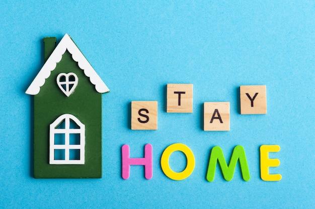 Grünes holzhaus und stay home-zeichen