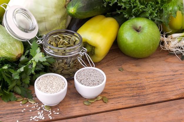 Grünes hypoallergenes gemüse in holzkiste und den samen. vegetarisches essen. selektiver fokus, draufsicht.