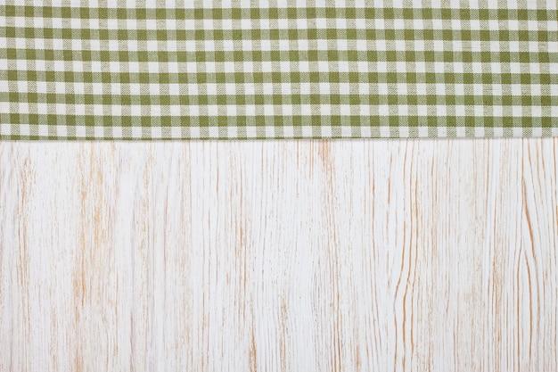 Grünes kariertes tischtuchtextil auf weißem holztischhintergrund. draufsicht, flach mit kopierraum, banner