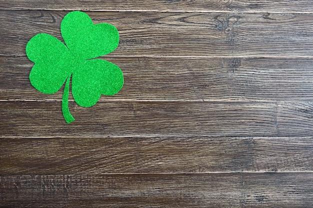 Grünes kleeblatt auf einem hölzernen hintergrund. st.patrick 's day hintergrund. symbol von irland. speicherplatz kopieren