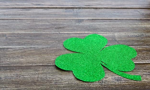 Grünes kleeblatt auf einem hölzernen hintergrund. st.patrick 's day hintergrund