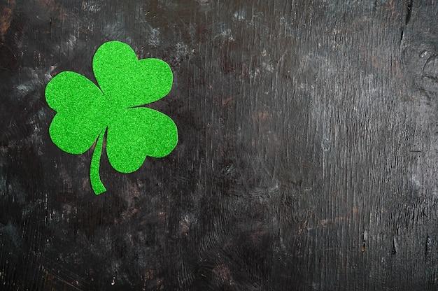 Grünes kleeblatt auf einem schwarzen hintergrund. st.patrick 's day hintergrund. symbol von irland. speicherplatz kopieren