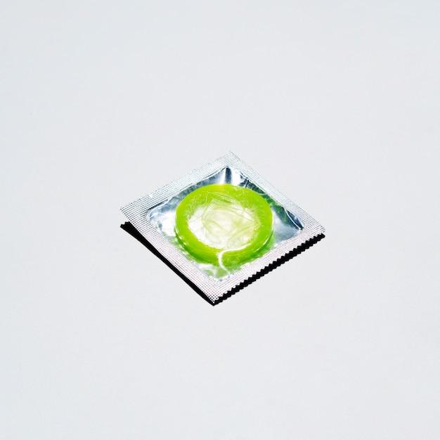 Grünes kondom des hohen winkels auf weißem hintergrund