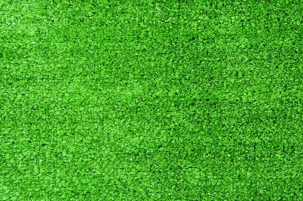 Grünes künstliches gras für beschaffenheitshintergrund