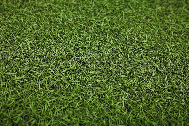 Grünes kunstrasen-fußballfeld. der grüne hintergrund.