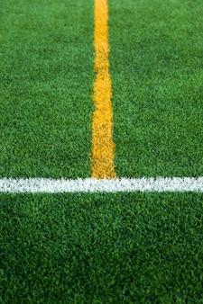 Grünes kunstrasen-fußballfußballfeld mit weißer und gelber liniengrenze