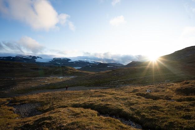 Grünes land, umgeben von hohen felsigen bergen mit der hellen sonne im hintergrund in finse, norwegen