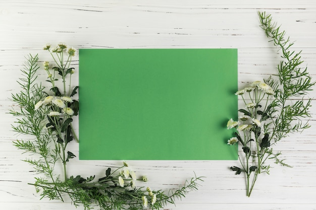 Grünes leeres papier mit chrysanthemenblumen und -blättern auf weißem hölzernem schreibtisch