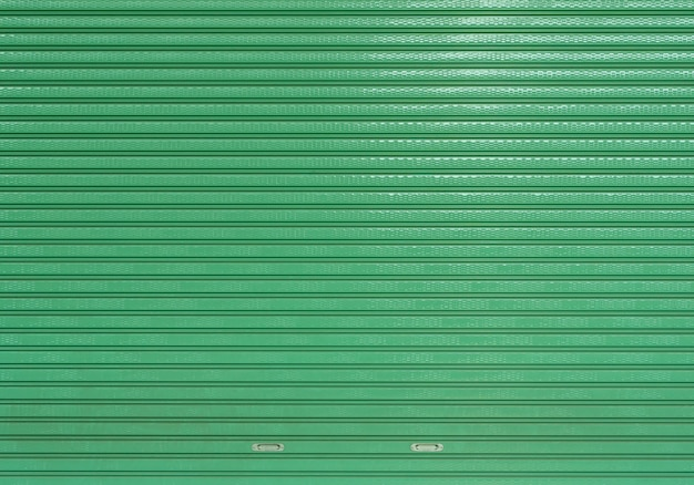Grünes leeres sauberes rolltorlager, abgestreifte blechtafelbeschaffenheit des autogaragengeschäft-eingangshintergrundes
