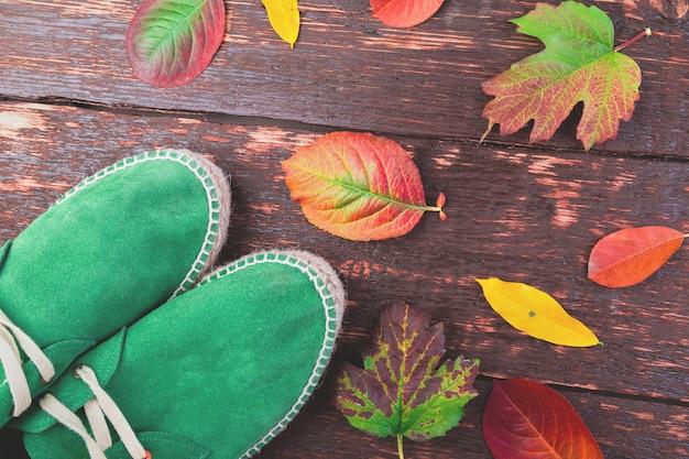 Grünes mannveloursleder lädt espadrilles auf hölzernem mit blättern auf