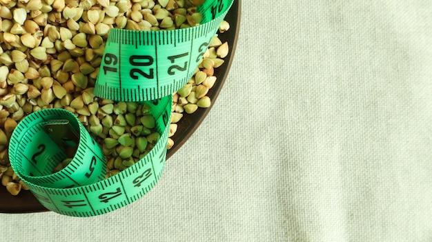 Grünes maßband auf einem raum des rohen buchweizens in einem gericht, konzept der diät und der gesunden ernährung