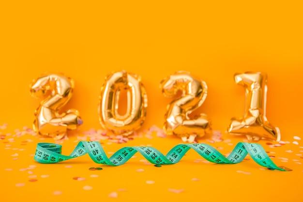 Grünes maßband auf orangefarbenen 2021 folienballons mit konfetti