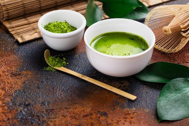 Grünes matcha teegetränk und teezubehör auf dunklem rostigem hintergrund