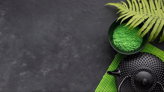 Grünes matchteepulver und farnblätter mit schwarzer teekanne auf schwarzem hintergrund