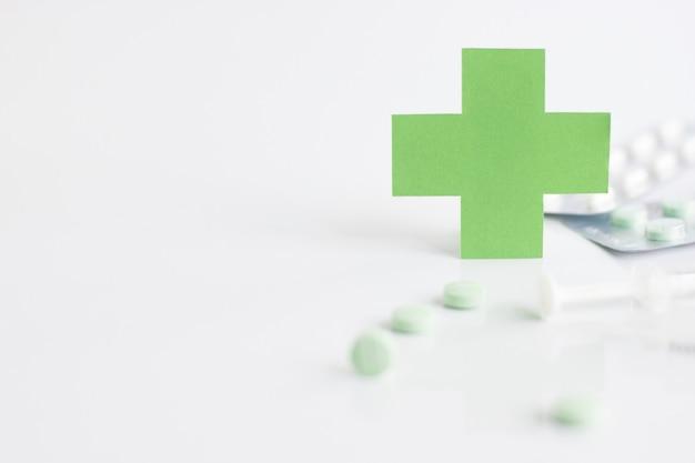 Grünes medizinisches quersymbol und spritze mit pille auf weißem hintergrund.