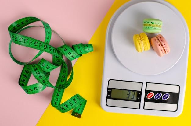 Grünes messendes band, digitale küchenwaage mit macarons auf gelbem und rosa. kein diät-tag