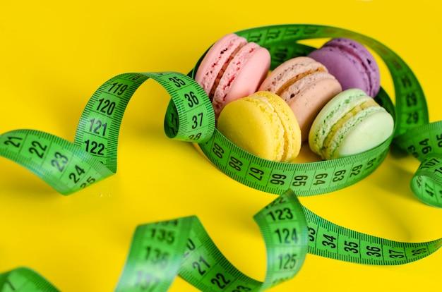 Grünes messendes band und macarons oder makronen auf gelb