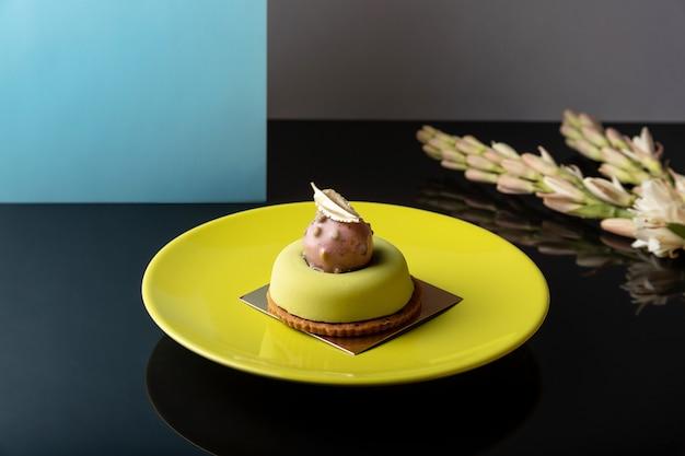 Grünes modernes rundes mousse-dessert auf glänzendem tisch