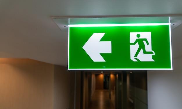 Grünes notausgangzeichen innen und büro