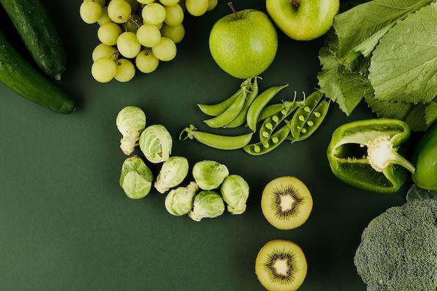 Grünes obst und gemüse auf dem tisch wie kiwi, äpfel, erbsen, trauben, pfeffer und rosenkohl