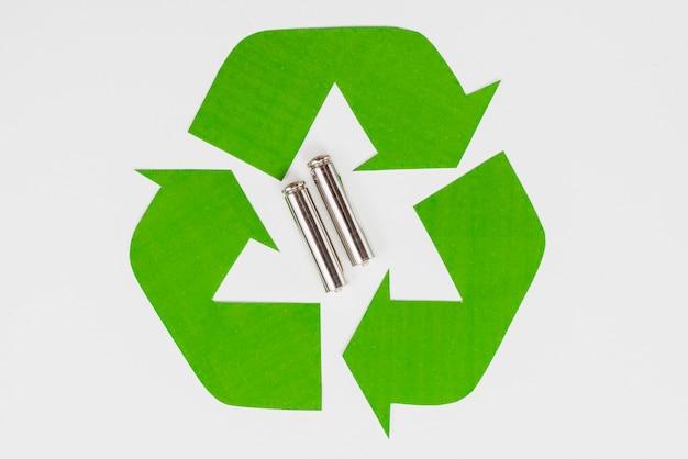Grünes öko-recycling-symbol und verbrauchte batterien