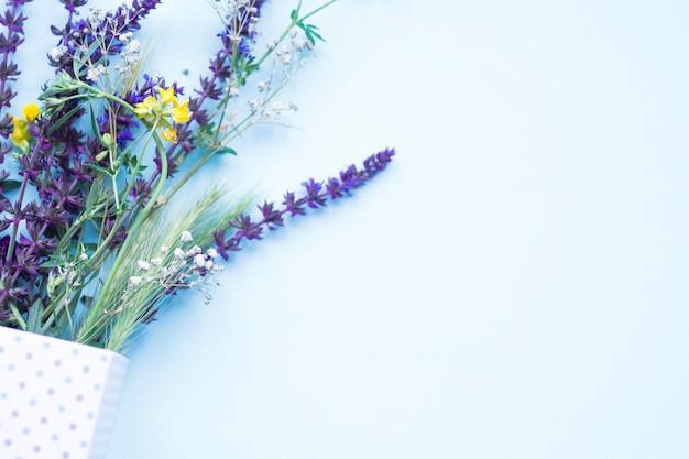 Grünes ohr des weizens und der blumen im tupfenkasten auf blauem hintergrund