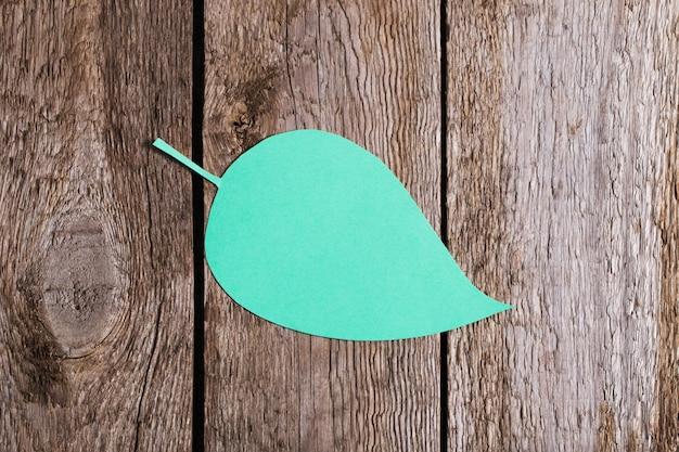 Grünes papierblatt auf hölzernem hintergrund