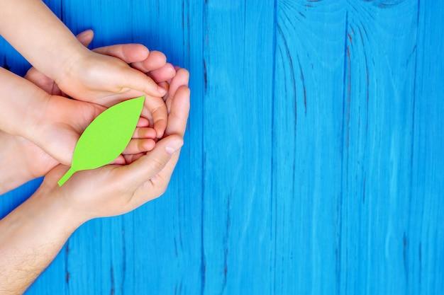 Grünes papierblatt in den händen des erwachsenen und des kindes.