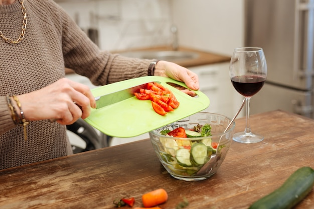 Grünes plastikbrett. genaue dame im beigen pullover, die gehackte tomaten in eine glasschüssel für den fertigen salat gibt