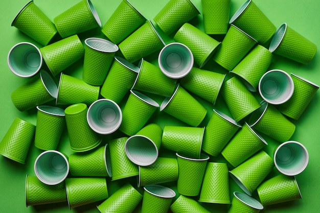 Grünes plastikwegwerfgeschirr auf grünem hintergrund