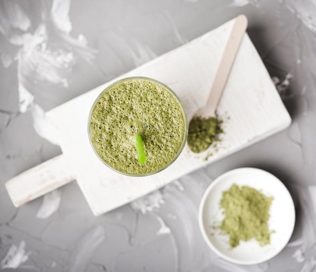 Grünes pulver und teigwaren auf hölzernem brett