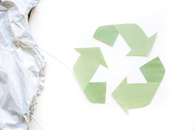 Grünes recycling-logo mit plastikmüll