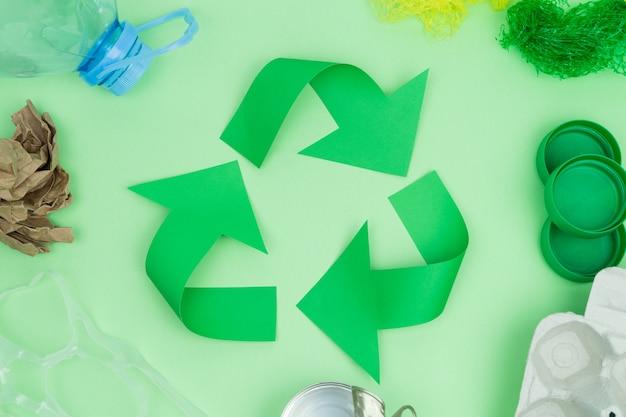 Grünes recycling-logo mit zu recycelnden gegenständen. recycling-konzept.