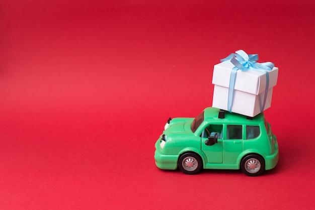 Grünes retro- spielzeugauto, das weißes geschenk auf rot mit copycopyspace liefert