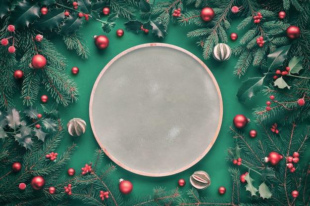Grünes rundes holztablett mit kopierraum, umgeben von tannen- und stechpalmenzweigen, schmuckstücken und dekorativen beeren mit trockenen limettenfrüchten.