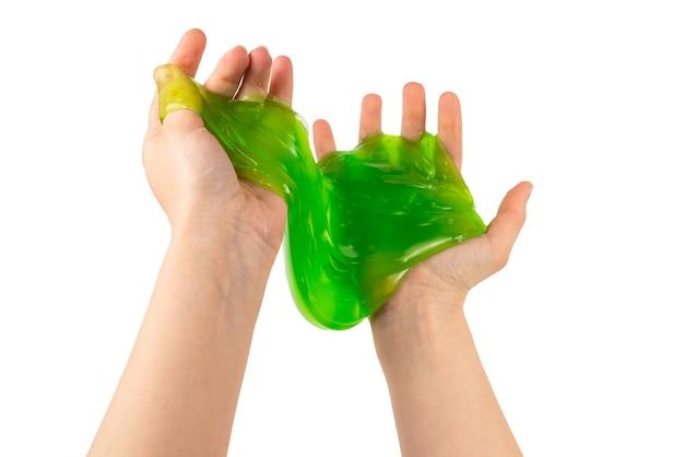 Grünes schleimspielzeug in der frauenhand lokalisiert auf weiß. draufsicht.