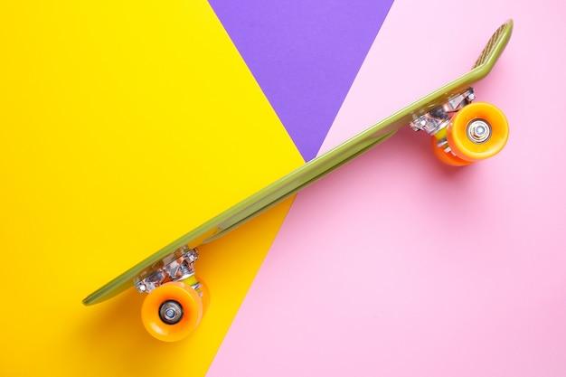 Grünes skateboard mit orange rädern auf gelbem, purpur und rosa. kunststoff mini cruiser board.
