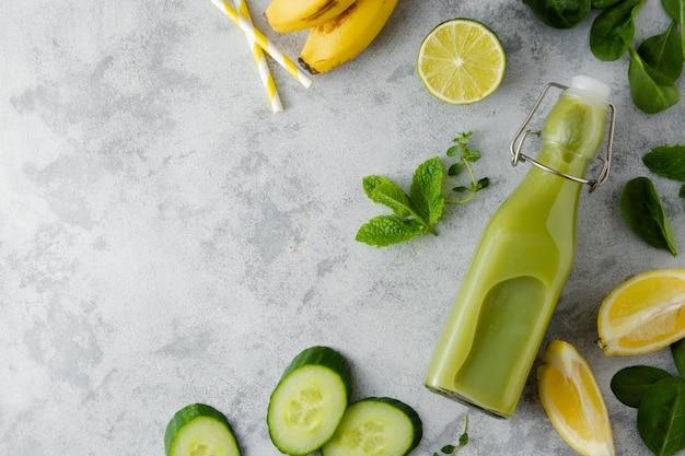 Grünes smoothie-detox-getränk in glasflasche mit frischem spinat, gurke, banane und limette. kopieren sie platz, ansicht von oben.
