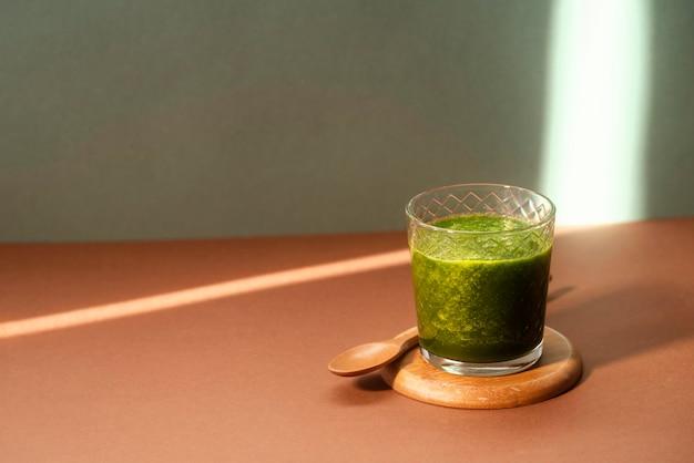 Grünes smoothie-glas mit hohem winkel