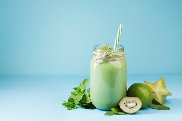 Grünes smoothieglas mit blauem hintergrund