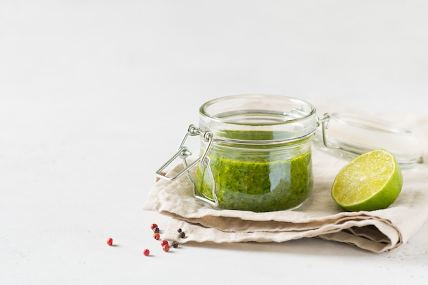 Grünes soße chimichurri mit frischem kraut und gewürzen im glas auf weißem hintergrund