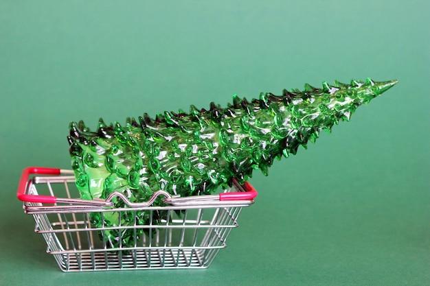 Grünes spielzeug weihnachtsbaum ein spielzeug befindet sich im einkaufskorb aus metall aus dem supermarkt.