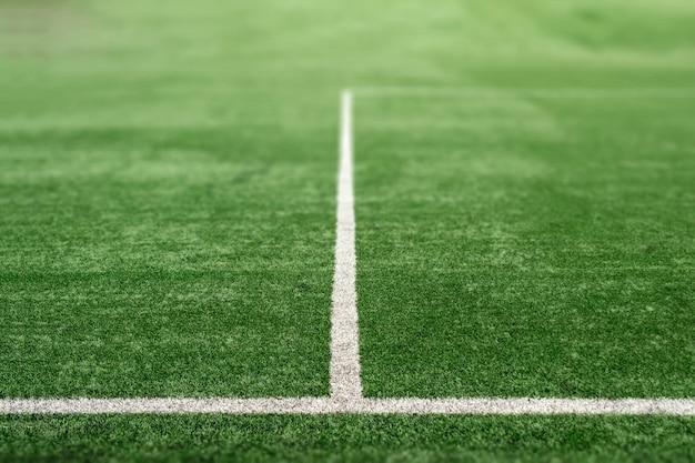 Grünes sportfeld mit kunstrasen, fußballplatzperspektive.