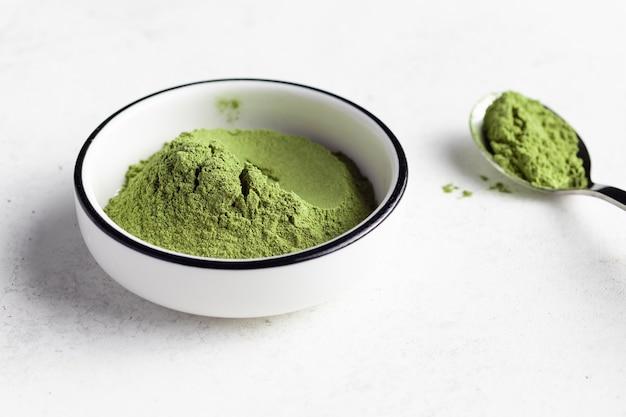 Grünes superfood-pulver in weißer schüssel