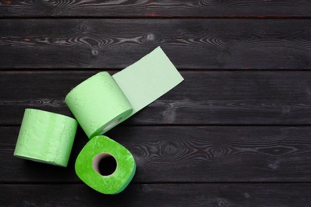 Grünes toilettenpapier rollt auf schwarzem hölzernem