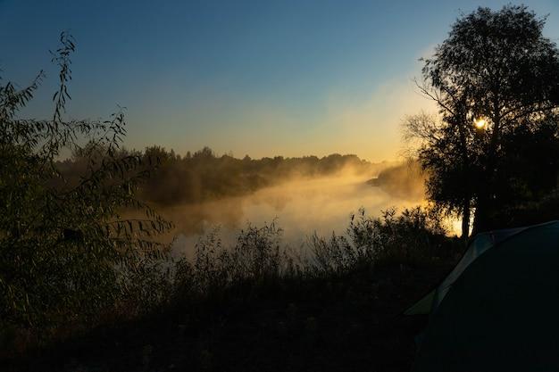 Grünes touristenzelt am fluss bei sonnenaufgang, mit morgendlichem herbstnebel auf dem wasser. touristische landschaft im freien.