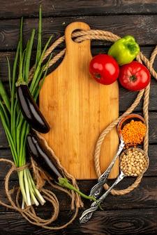 Grünes und gewürztes frisches vitamin, reich an roten tomaten, schwarzen auberginen und grünem paprika auf einem braunen rustikalen holzboden