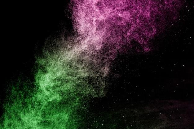 Grünes und rosa pudereffektspritzen für maskenbildner oder grafikdesign im schwarzen hintergrund